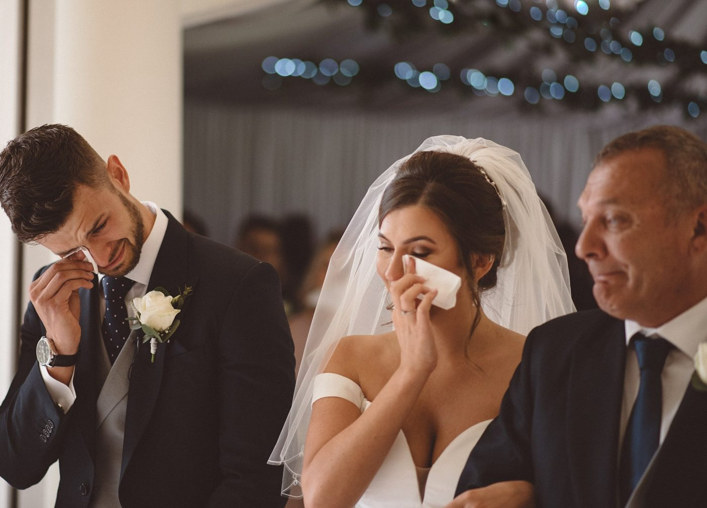 Emotional bride, groom & father of the bride