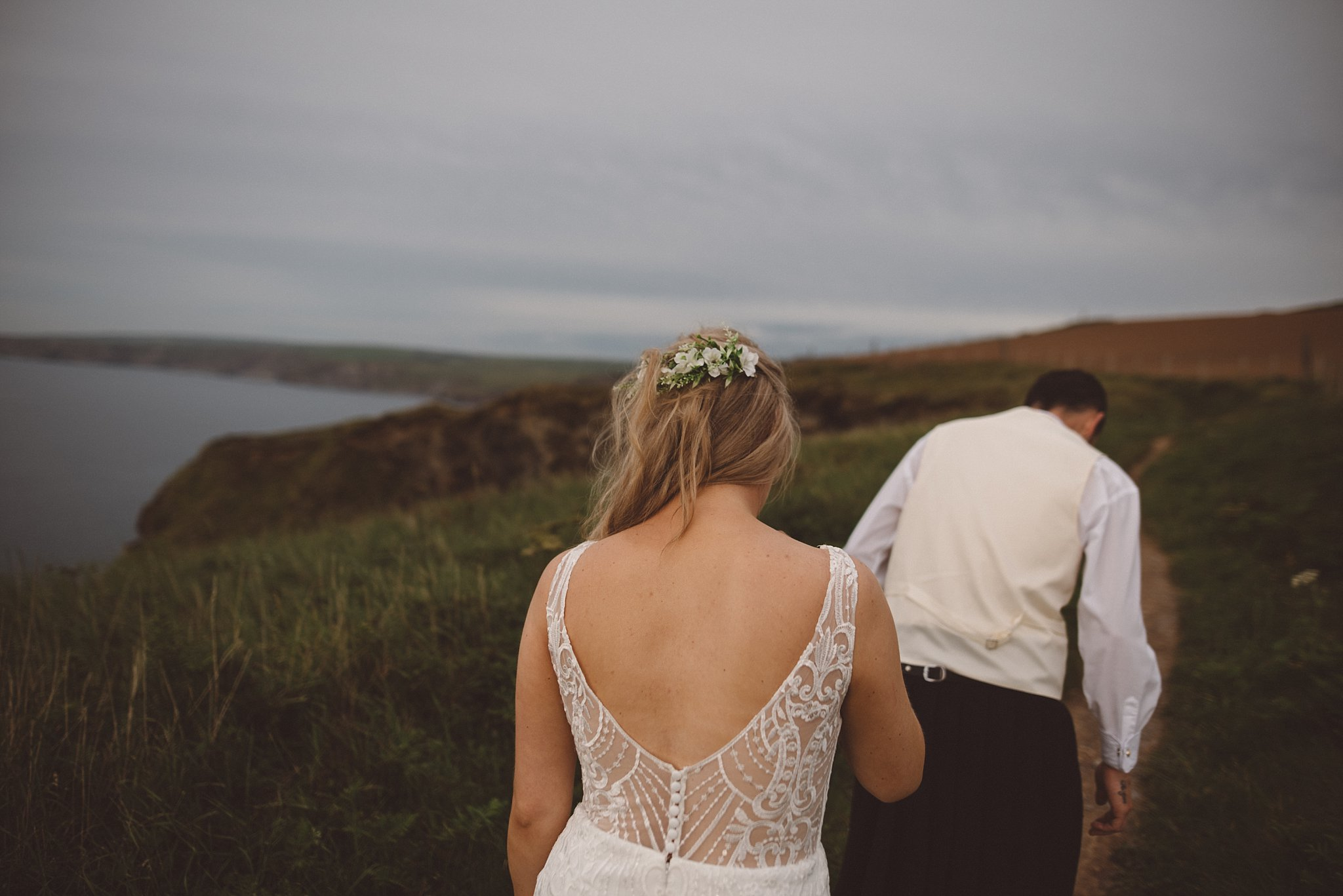 Bride and Groom walking along the Cornish coast at Port Isaac