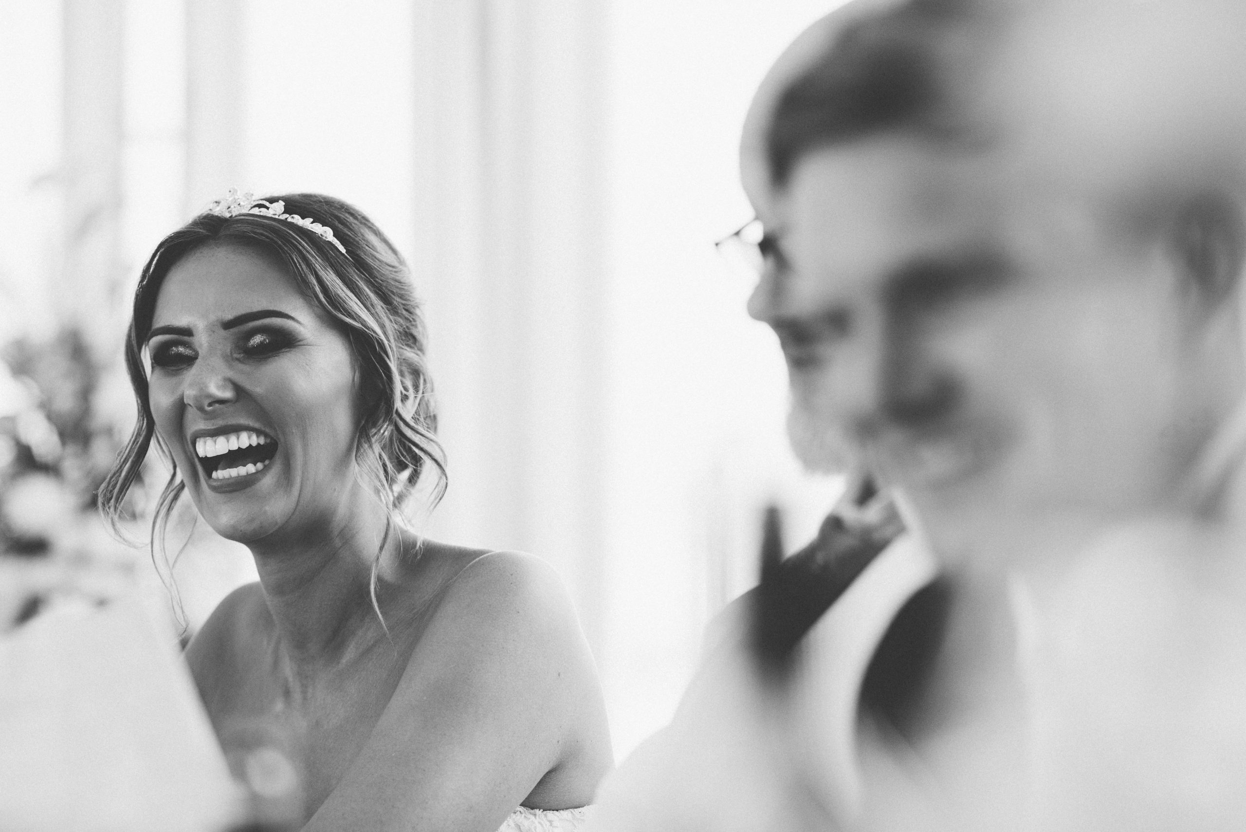 Laughing bride at Keythorpe Manor wedding speeches