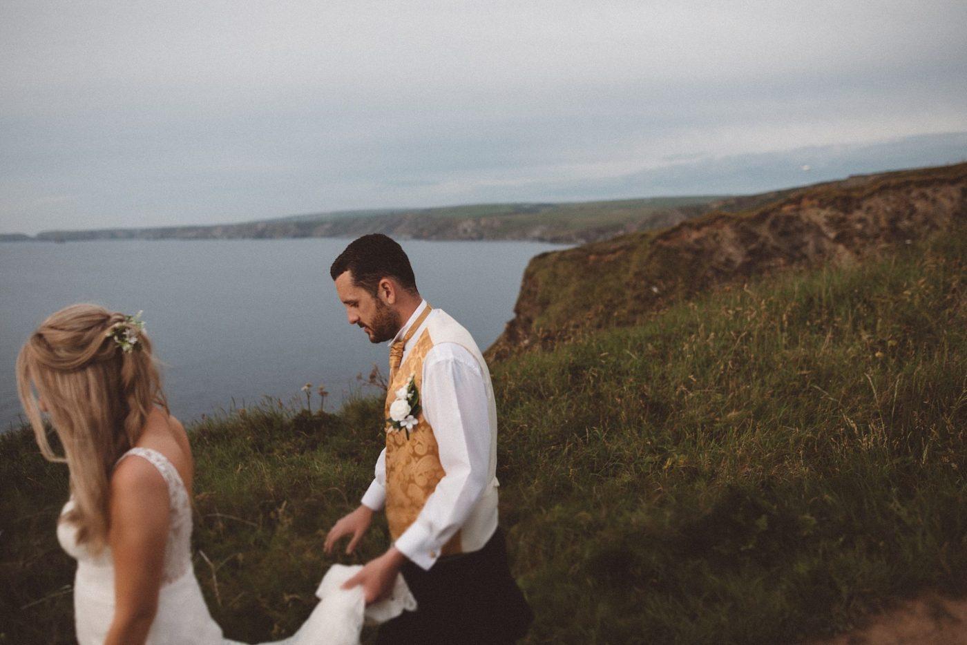 bride and groom walking the Port Isaac Cornish coast
