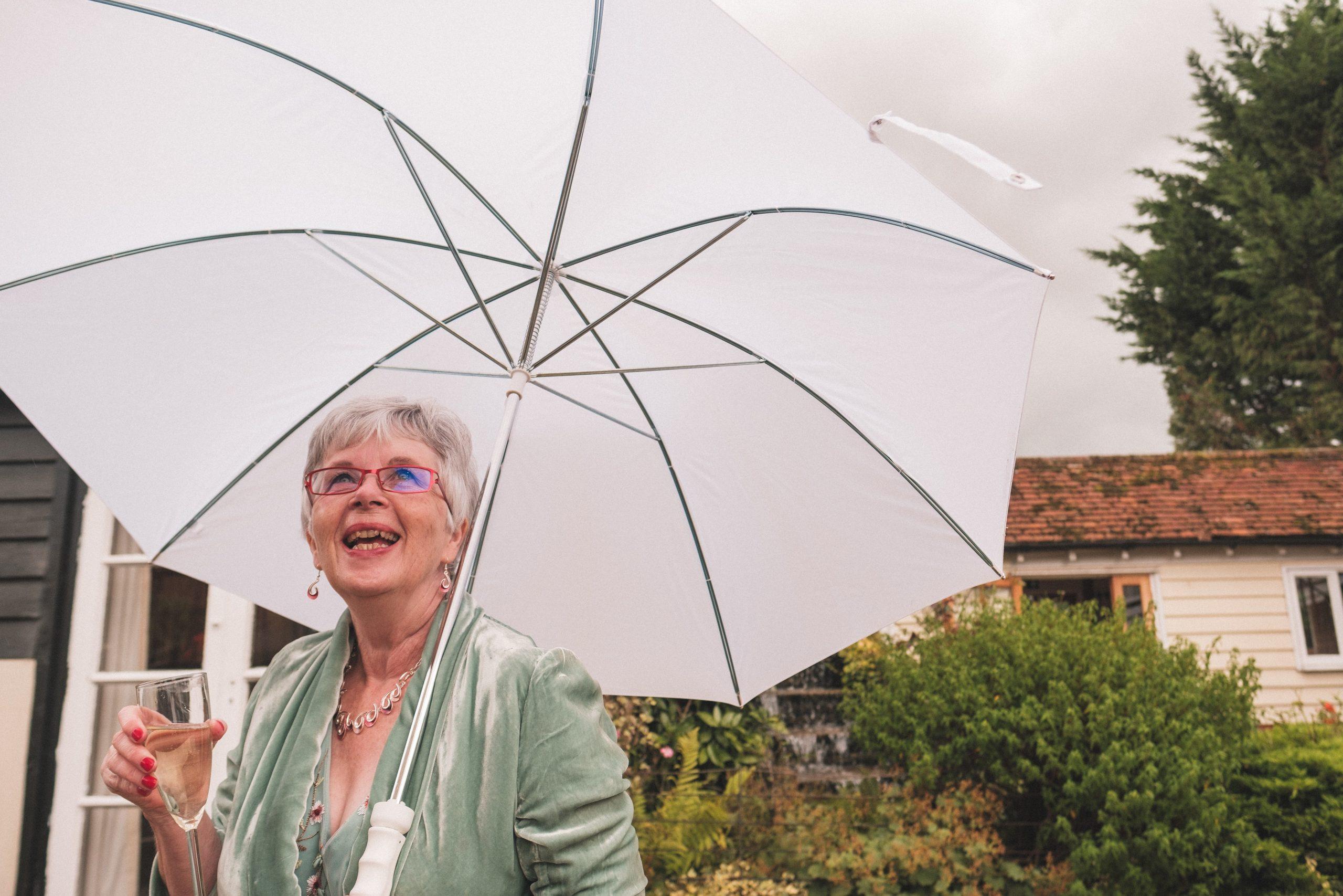 wedding guest with umbrella during a rainy Essex wedding
