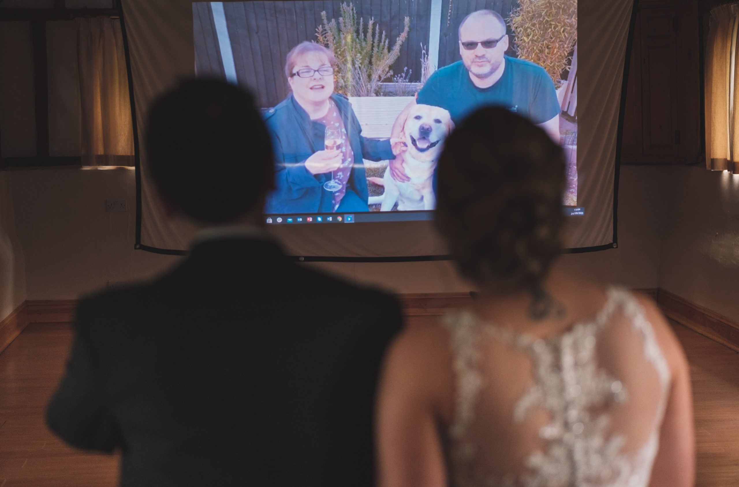 bride and groom watching loved ones on projector