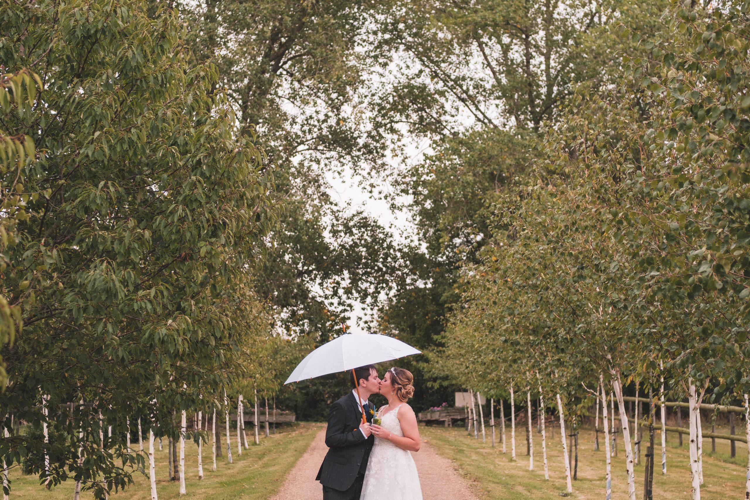 bride and groom with umbrella at Essex wedding